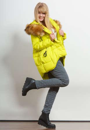 ropa de invierno: Hermosa joven sonriente chica de moda el uso de chaqueta con capucha presenta aumento de la pierna. Preparar a sí misma ropa. Moda en época de invierno. Foto de archivo