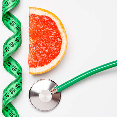weightloss: Diet healthy eating weight control concept. Grapefruit with measuring tape and stethoscope on white scales