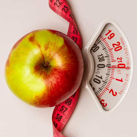 WEIGHT: Dieting healthy eating slim down concept. Closeup apple with measuring tape on weight scale