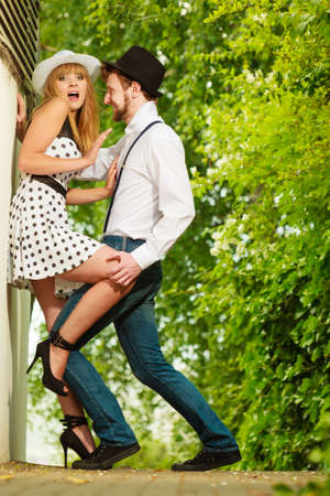 Summer holidays love relationship and dating concept - romantic playful couple retro style flirting outdoor Stock Photo