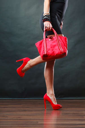 mujeres elegantes: Celebración concepto de moda noche. Mujer en rojo corto vestido de negro claveteado de celebración de zapatos del bolso, las piernas de mujer con tacones en el suelo del partido