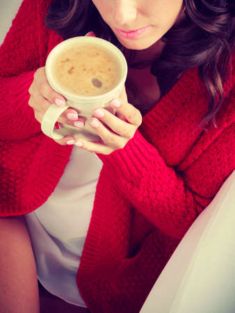 red cardigan: Attractive fall girl red autumnal sweater holding white mug with coffee warm beverage, sitting on sofa at home. Woman warming herself relaxing top view