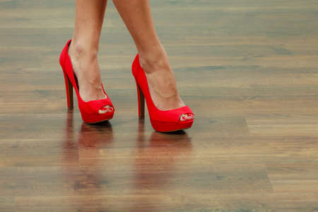 Female fashion. Closeup red high heels spiked fashionable shoes on female legs 写真素材