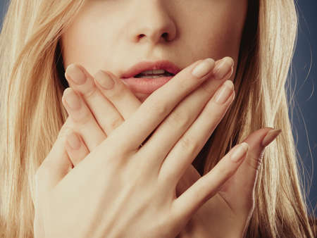 Speak no evil concept. Surprised woman face covering her mouth with hands close up Stock Photo