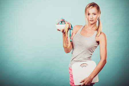 weight control: Diet, healthy eating and slim body concept. Fit fitness girl holding bowl with many colorful measuring tapes as dieting symbol and weight scales studio shot on blue