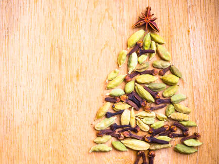 cardamon: Christmas tree made from spices anise star cardamon pods and cloves on wooden background