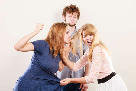 wooing: Aggressive mad women fighting over man pulling hair. Jealous girls wooing guy. Violence.