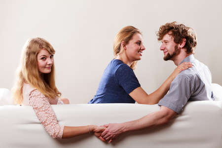 cheater: Betrayal and infidelity concept. Handsome boy with two attractive blondie girls. Man cheating women by mislead chosen one and flirting with another female.