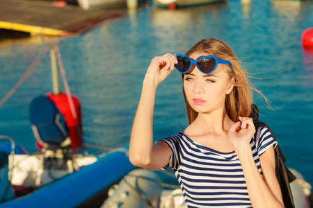 breeze: Summer relaxation concept.. Portrait girl with blue heart shaped sunglasses enjoying summer breeze outdoor in marina Stock Photo