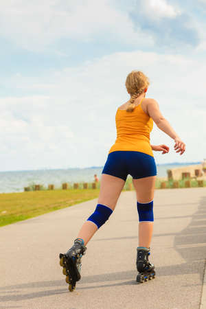 rollerblades: Holidays, active lifestyle freedom concept. Young fit woman on roller skates riding outdoors on sea coast, girl rollerblading on sunny day Stock Photo