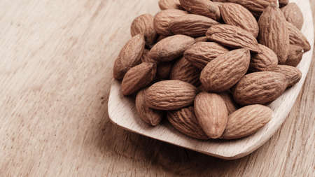 whole food: Whole food, good for health. Almonds on wooden spoon kitchen board background