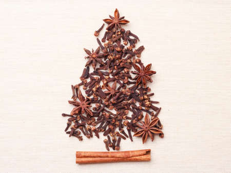 Christmas tree made from brown spices cinnamon stick anise stars and cloves on burlap background