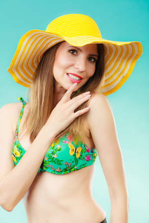 model portrait: Summer holidays concept. Closeup woman in yellow hat bikini portrait on vivid blue background
