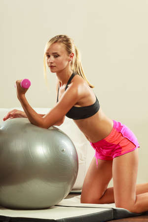 gym ball: Healthy active lifestyle. Fitness woman with gym ball and dumbbell doing exercise Stock Photo