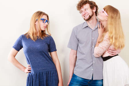 cheated: Jealousy and betrayal concept. Abandoned jelous girl watching on happy couple - young attractive blondie woman kissing handsome boy. Stock Photo