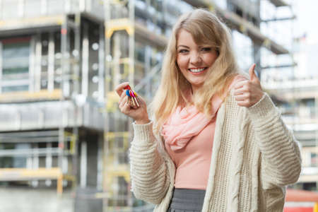 thumb keys: Real estate concept - young woman on front of new big modern house building construction site with keys making thumb up sign gesture Stock Photo
