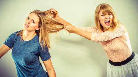 blonde girls: Aggressive mad women fighting each other pulling hair. Two young girls struggling win catfight. Violence.