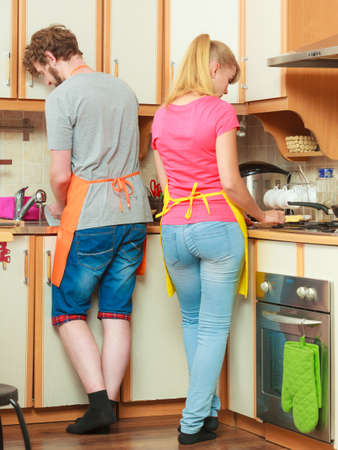 tidying up: Couple woman and man in apron cooking preparing dinner food and washing up in kitchen together.