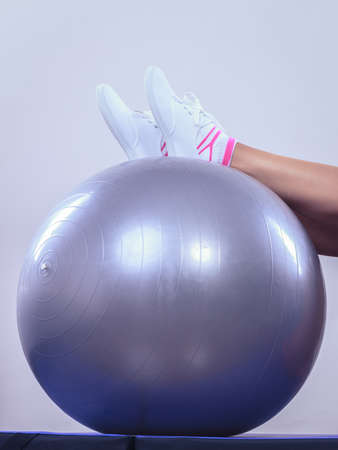girl sport: Sport, training, gym and lifestyle concept. Female legs in sneakers on fitball, woman in sportswear doing fitness exercises with fit ball at home