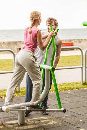 escucha activa: Mujer activa que ejercita en la m�quina el�ptica y el hombre escucha m�sica. chica deportiva ajuste feliz en traje de entrenamiento que se resuelve en un gimnasio al aire libre. la aptitud del deporte y el concepto de estilo de vida saludable.