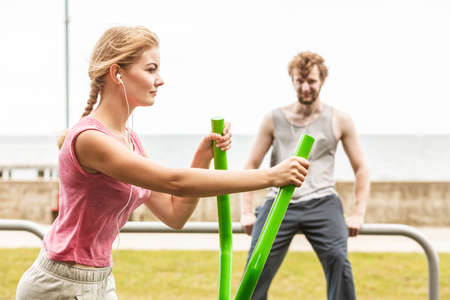 active listening: Active woman exercising on elliptical trainer machine and man listening to music at outdoor gym. Sport fitness. Stock Photo