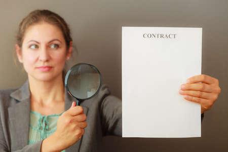 contrato de trabajo: Los contratos y acuerdos concepto. belleza de la mujer adulta en la celebración de la chaqueta muestra el contrato. Cerrar un retrato de la persona con la lupa el estudio de acuerdo.