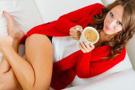 girl sitting: Attractive fall girl red autumnal sweater holding white mug with coffee warm beverage, sitting on sofa at home. Woman warming herself relaxing top view