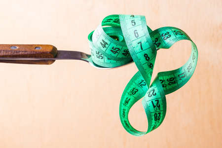 centimeter: Diet food healthy lifestyle and slim body concept. Closeup green measuring tape centimeter on kitchen spoon