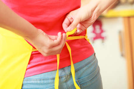 apron: Closeup of woman tying apron up. Girl person cooking.