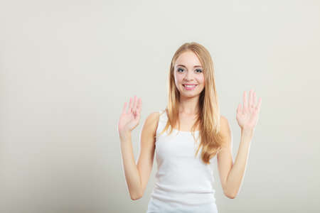 woman hands up: Blonde girl spreading hands with joy, happy successful young woman with arms up. Success positive emotions. Stock Photo