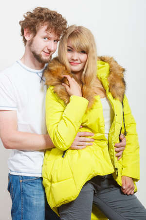 warm shirt: Happy joyful couple posing in studio. Young woman in warm lime jacket and man in white shirt. Winter autumn fall fashion.