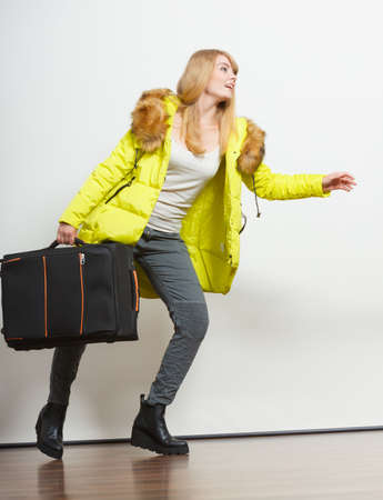 running late: Young woman in warm jacket with suitcase running late. Gorgeous blonde tourist travel girl. Tourism.