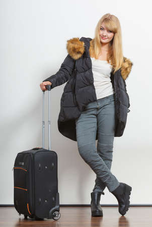 warm jacket: Happy young woman in warm jacket with suitcase. Gorgeous blonde tourist travel girl. Tourism. Stock Photo