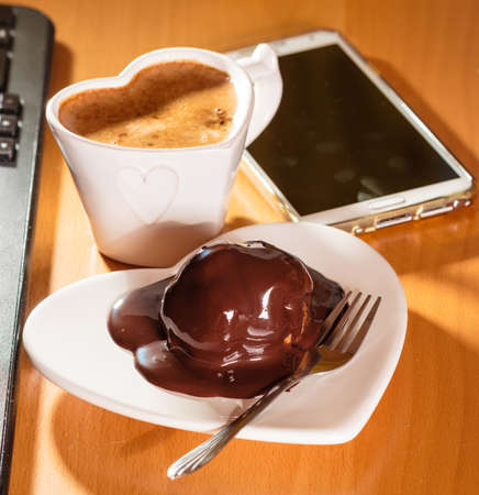 heart work: Cup of coffee and chocolate cake on heart shaped plate saucer next to laptop notebook computer keyboard and smartphone. Office work desk.