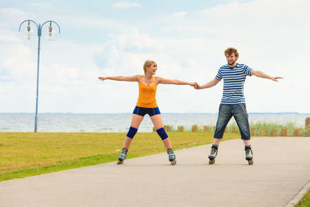 inline skater: Active lifestyle people and freedom concept. Young fit couple on roller skates riding outdoors on sea coast, woman and man rollerblading enjoying time together