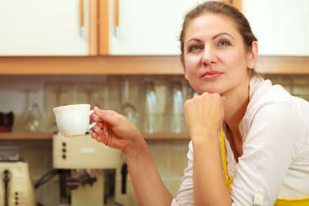 energizing: Pensive mature woman holding cup of coffee in kitchen. Housewife female with hot energizing beverage. Caffeine energy. Stock Photo