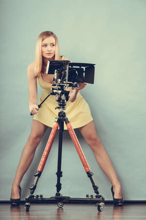 sexual girl: Photographer girl shooting images. Attractive fashionable blonde woman in full length taking photos with camera on blue