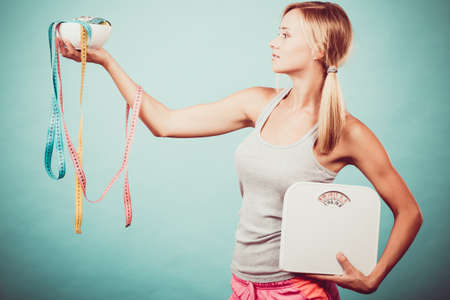fat and slim: Diet, healthy eating and slim body concept. Fit fitness girl holding bowl with many colorful measuring tapes as dieting symbol and weight scales studio shot on blue