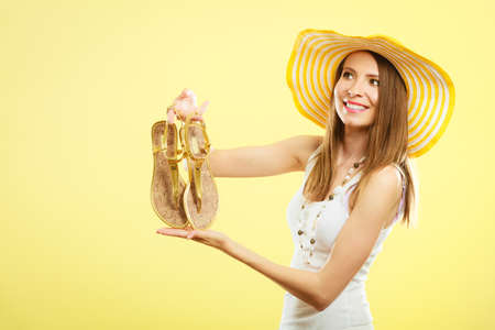 female soles: Holidays summer fashion concept. Woman in big yellow hat holding golden sandals in hand bright background. Stock Photo