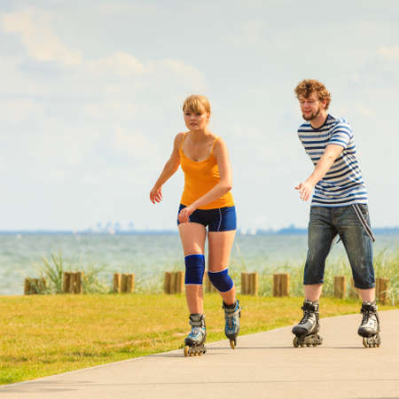 rollerblades: Active lifestyle people and freedom concept. Young fit couple on roller skates riding outdoors on sea coast, woman and man rollerblading enjoying time together