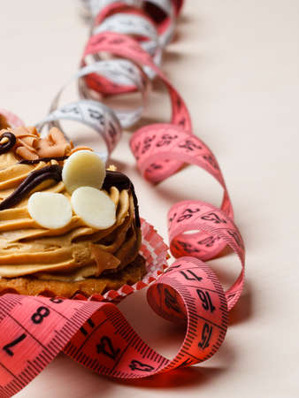 fattening: Appetite and gluttony concept. Fattening problem. Cake cupcake with measuring tapes on table