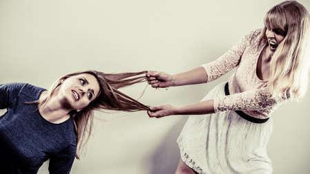 femme chatain: Folles agressifs combattre les uns les autres de tirer les cheveux. Deux jeunes filles en difficulté victoire catfight. La violence. Banque d'images