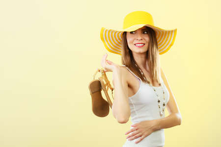 girl soles: Holidays summer fashion concept. Woman in big yellow hat holding golden sandals in hand bright background. Stock Photo