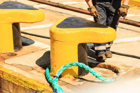 mooring bollard: harbor quayside yellow mooring bollard with blue rope in marina outdoor