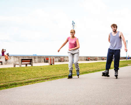rollerskating: Active young people friends in training suit rollerskating outdoor. Woman and man riding enjoying sport.