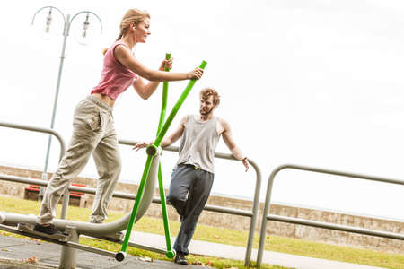 active listening: Active woman exercising on elliptical trainer machine and man listening to music. Fit sporty girl in training suit working out at outdoor gym. Sport fitness and healthy lifestyle concept.