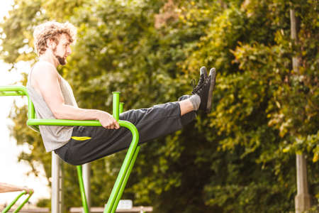 Active young man exercising on leg raise. Muscular guy in sports training suit outdoor working out at the gym. Sports fitness and healthy lifestyle concept.