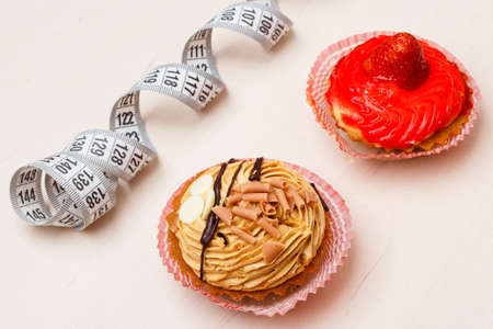 fattening: Appetite and gluttony concept. Fattening problem. Cakes cupcakes with measuring tape on table