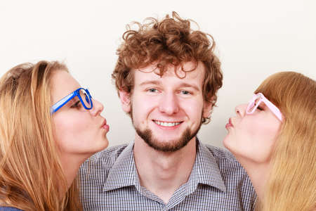unfaithful: Two pretty young women in glasses kissing handsome man. Love triangle.
