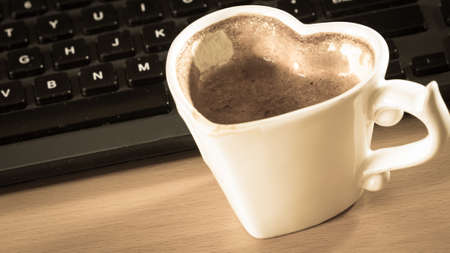 heart work: Heart shaped mug cup of coffee next to laptop notebook computer keyboard. Office work desk.